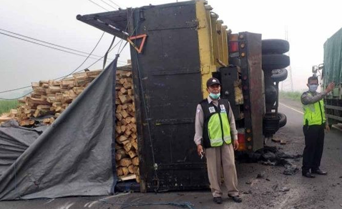 Truk fuso bermuatan kayu sengon, yang terguling di Jalan Raya Porong, Selasa (31/3)